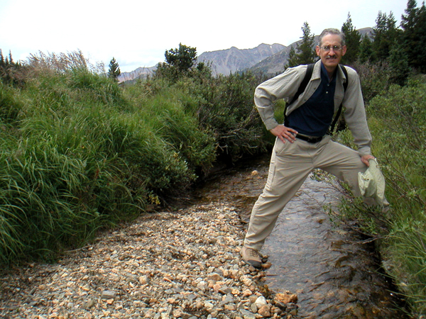 Straddling the beginning of the Colorado River at the summit of La Poudre Pass after hiking the Colorado River Trail through Shiper Park and the site of Lulu City